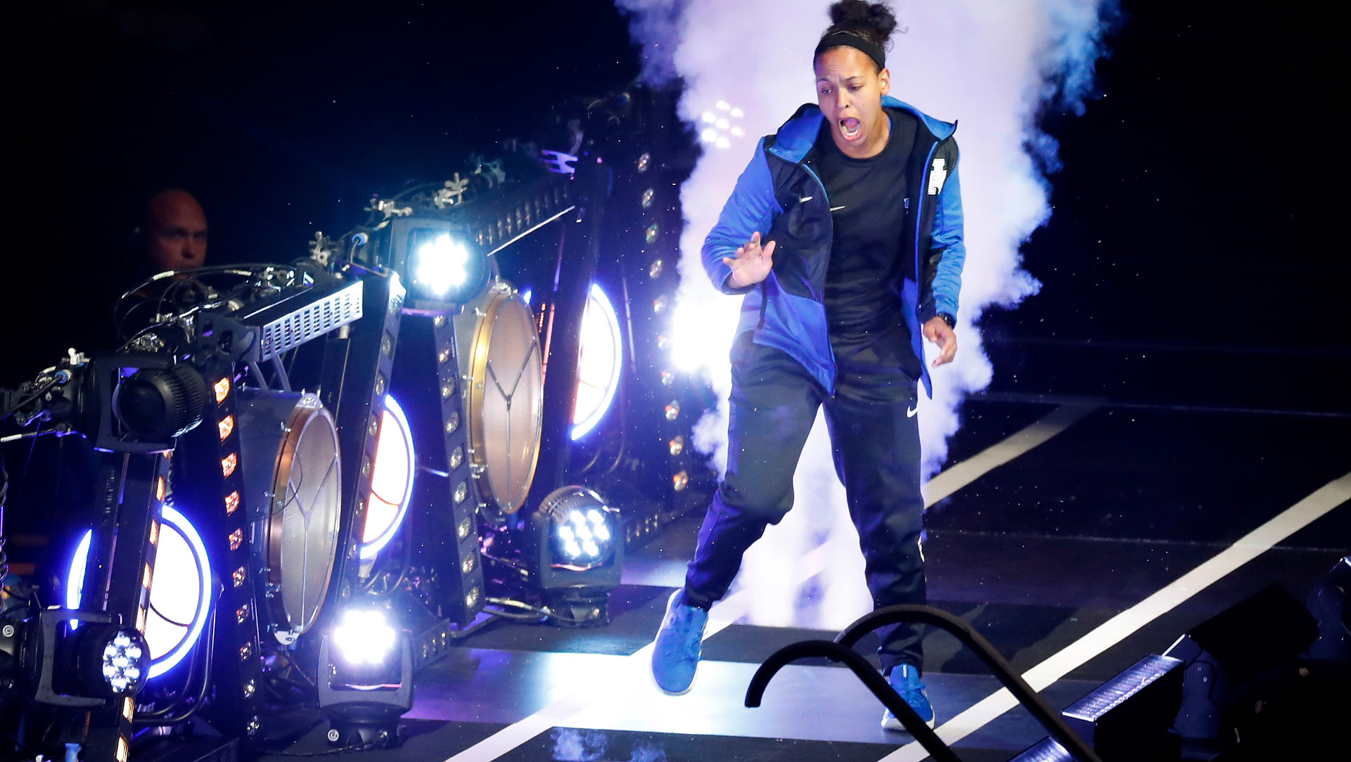 Amber, dressed in a black and blue sweatsuit, dances down a ramp of lights, clocks and fog machines at Big Blue Madness.