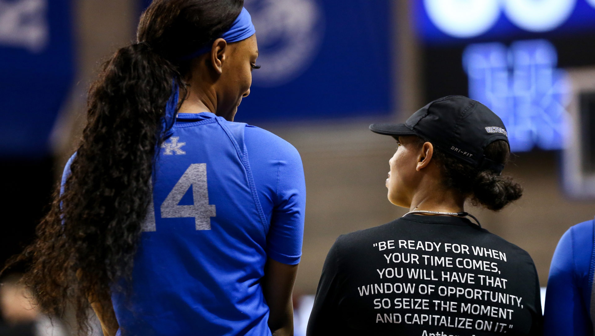 """A photo of Amber and a player with their backs to the camera, talking and smiling before a game. Amber's shirt says """"Be ready for when your time comes. You will have that window of opportunity."""""""