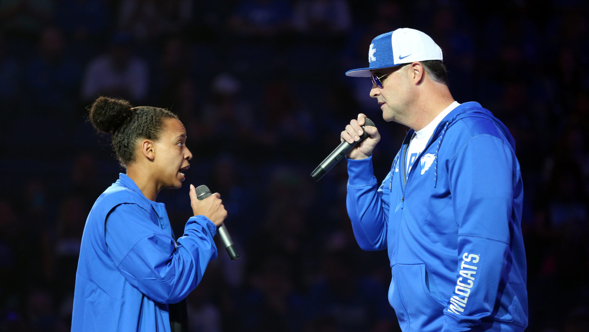 Amber and Coach Mitchell, dressed in UK jackets, both holding microphones and talking to each other during Big Blue Madness.