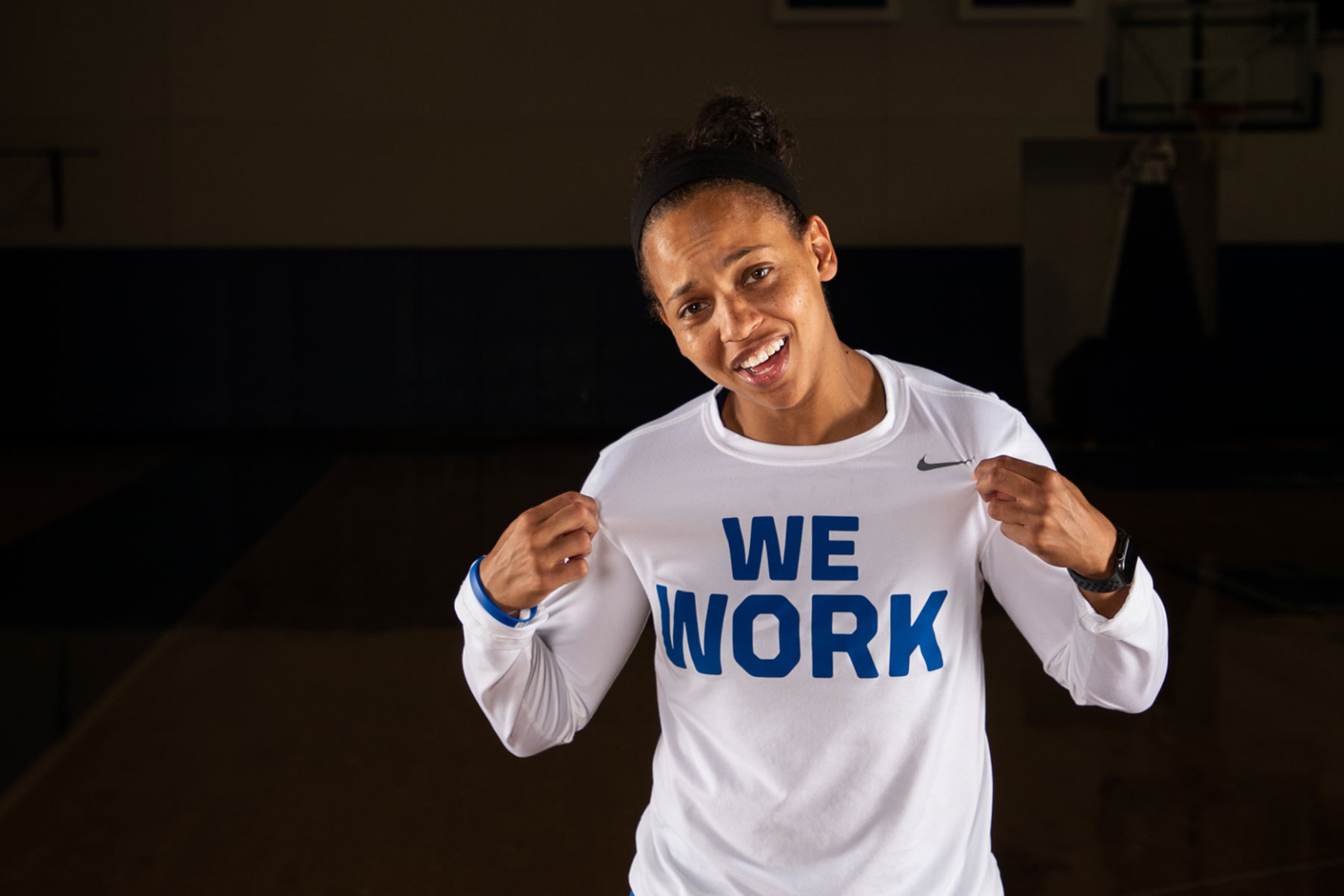 A portrait photo of Amber Smith, a young, athletic Black woman with her dark brown in a bun, wearing a white long sleeved shirt with 'WE WORK' on the front in royal blue letters.