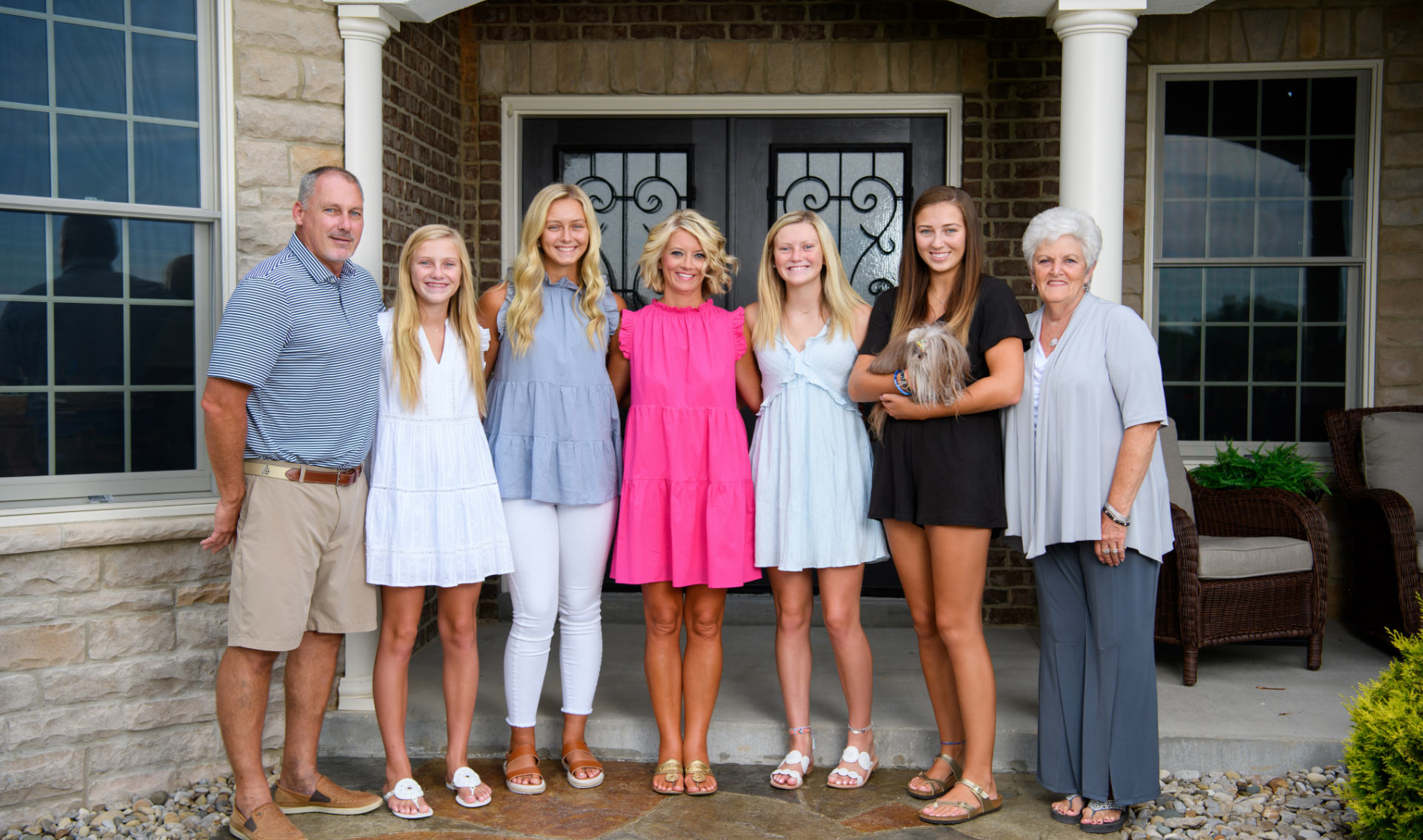 Angela and her family, including her four daughters, her husband, her mother, and their dog, pose for a photo outside their front door.
