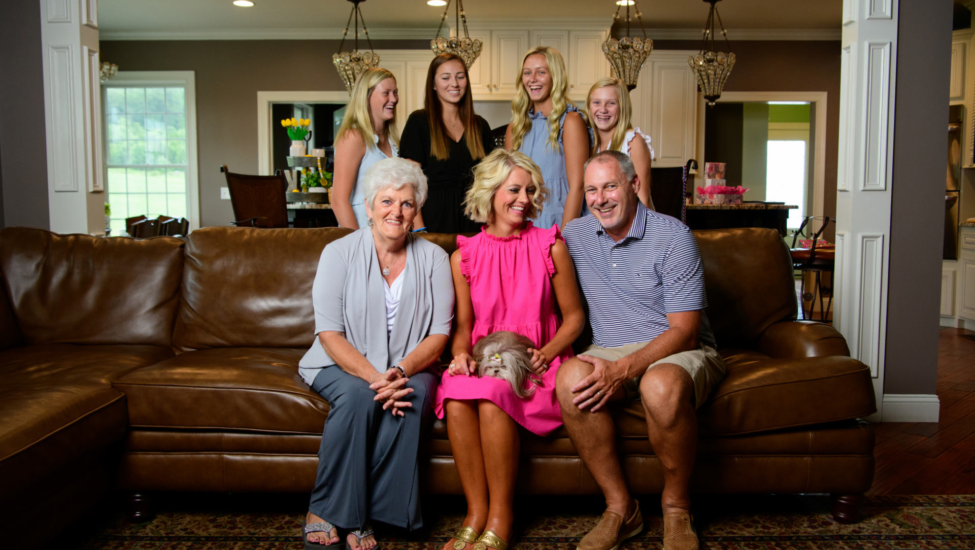 Angela and her family pose for a photo in their living room. She is flanked by her husband and her mother, with her four teenage daughters standing behind them. Angela has a small fluffy dog on her lap.