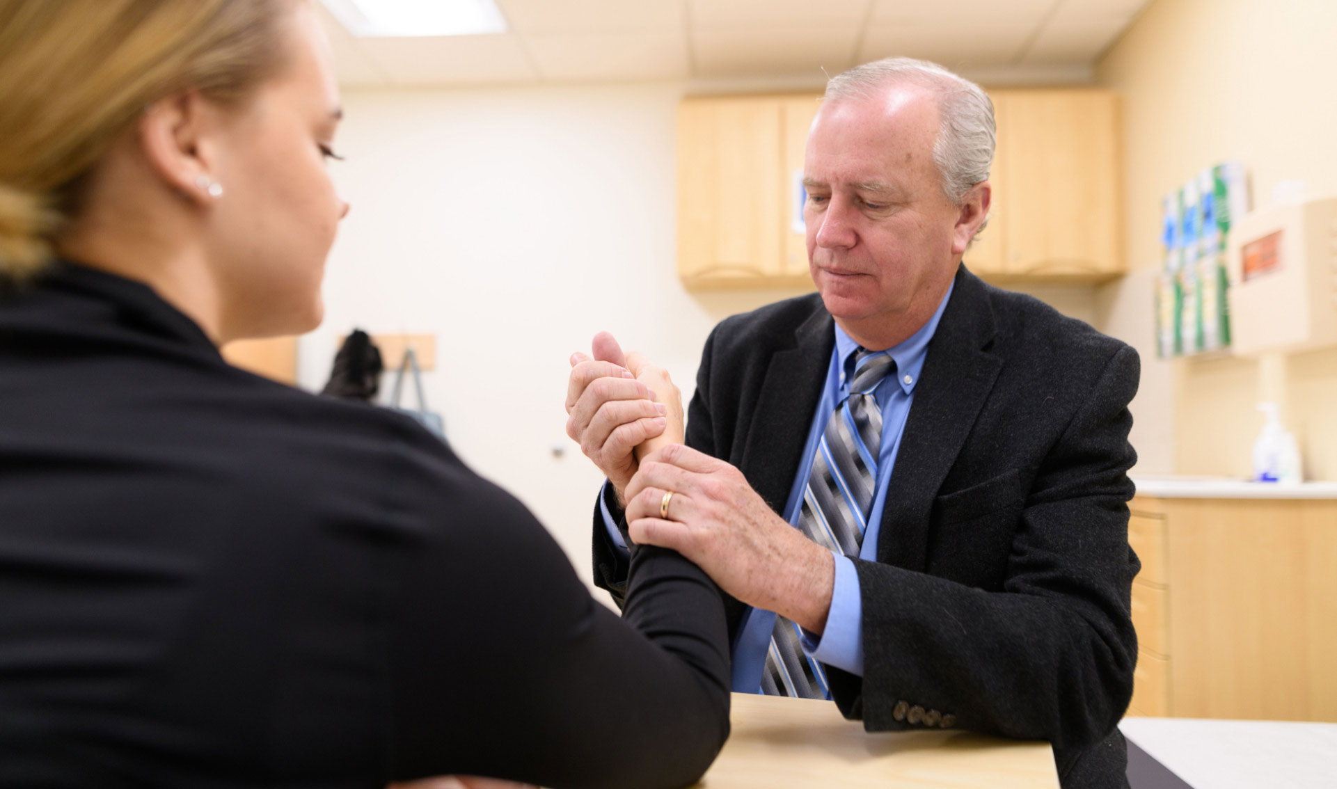 Dr. David Drake, an older man dressed in a blue button-up shirt, striped tie, and black suit jacket is seen appearing to help a young woman with her hand and fingers as he works intently.