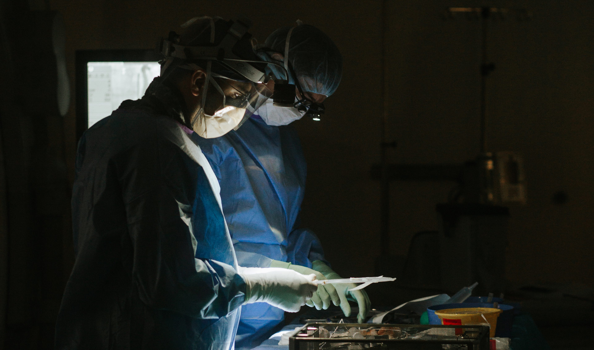 Dr. Gurley and a colleague perform a surgery. The photo features dramatic lighting and a dark background.