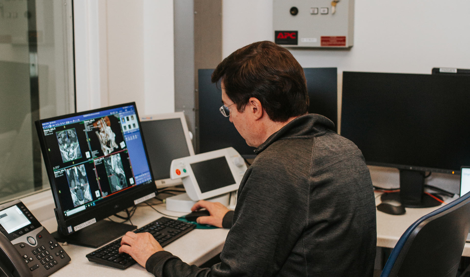 Dr. Gurley, dressed in a gray collared long-sleeve pullover, with his back facing the camera as he examines x-rays on a computer monitor.