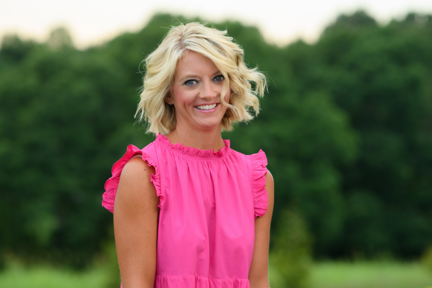 Angela King, a young-looking middle-aged woman with short, wavy blonde hair, poses for a portrait in an outdoor setting. She is wearing a ruffly pink sleeveless dress and smiling.