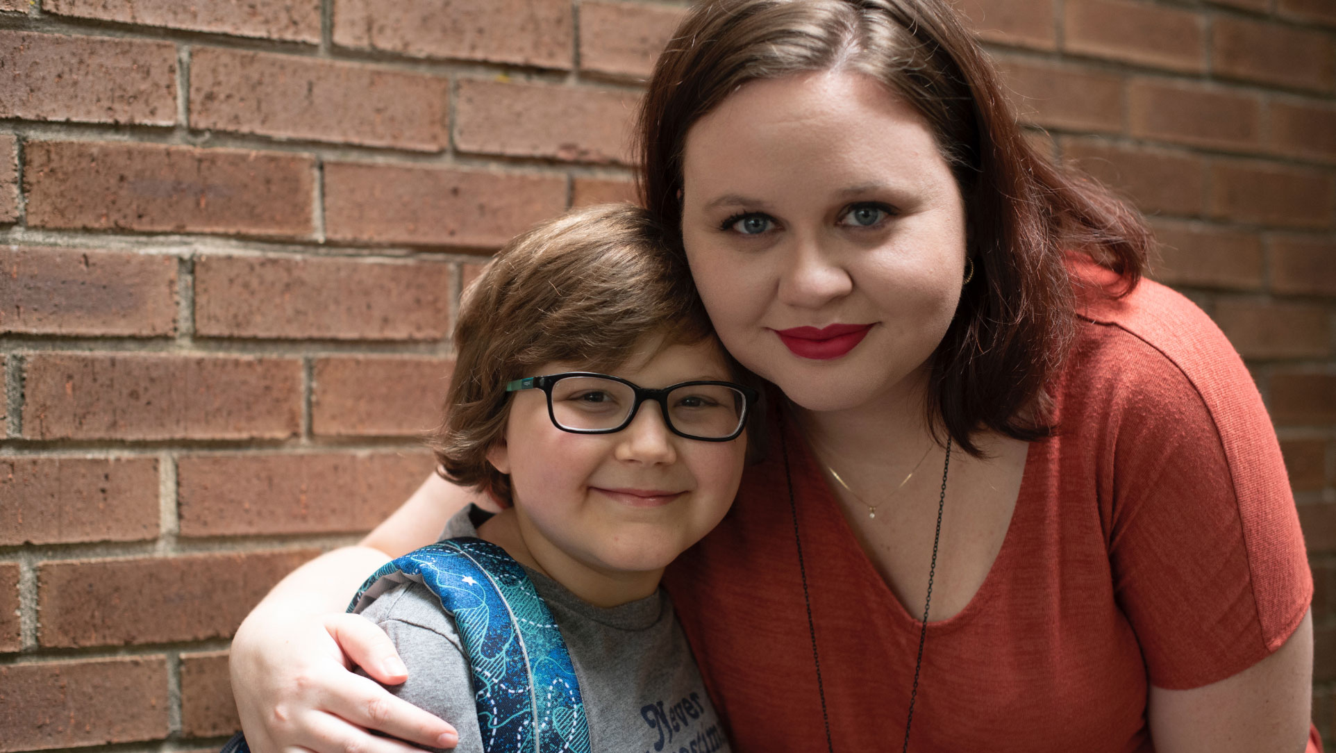 A photo of Ellie and her mom, Morgan, a young looking woman with brown hair wearing red lipstick and an orange shirt. Morgan's arm is around Ellie's shoulders. Both are smiling.