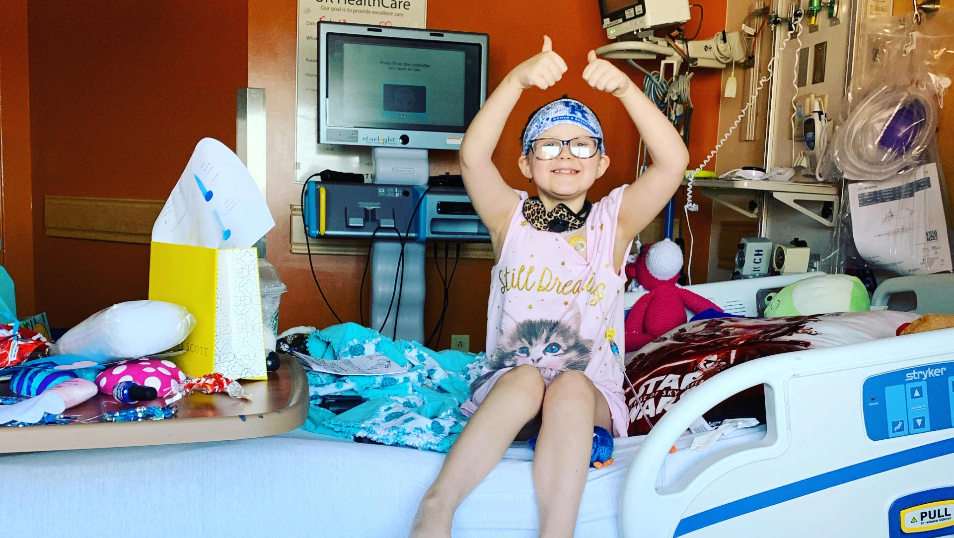 A photo of Ellie in her hospital room where she is sitting upright on the bed with both arms in the air giving two thumbs ups. Her room is full of colorful blankets, stuffed animals, and a yellow gift bag on her bed.