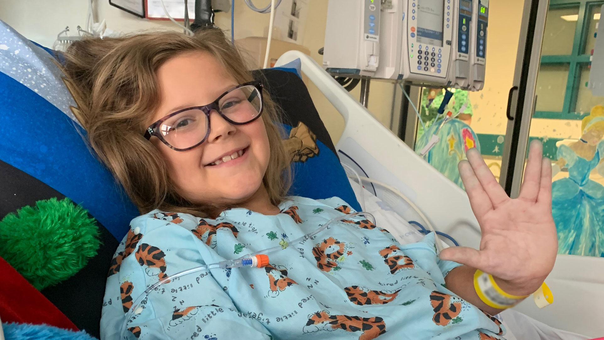 """A close-up photo of Ellie laying in her hospital bed smiling at the camera while giving the Star Trek """"live long and prosper"""" hand symbol for the photo. She is wearing a blue gown with cartoon tigers on it."""