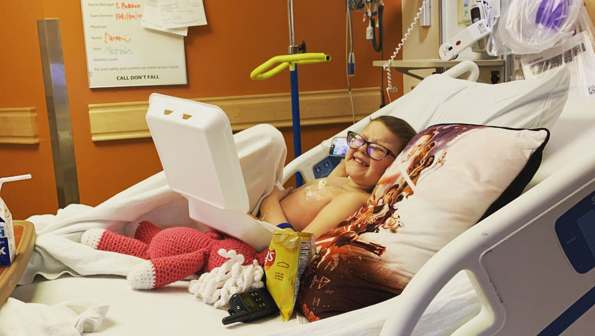 An older photo of Ellie laying in her hospital bed, enjoying a snack and giving the camera a cheesy smile.