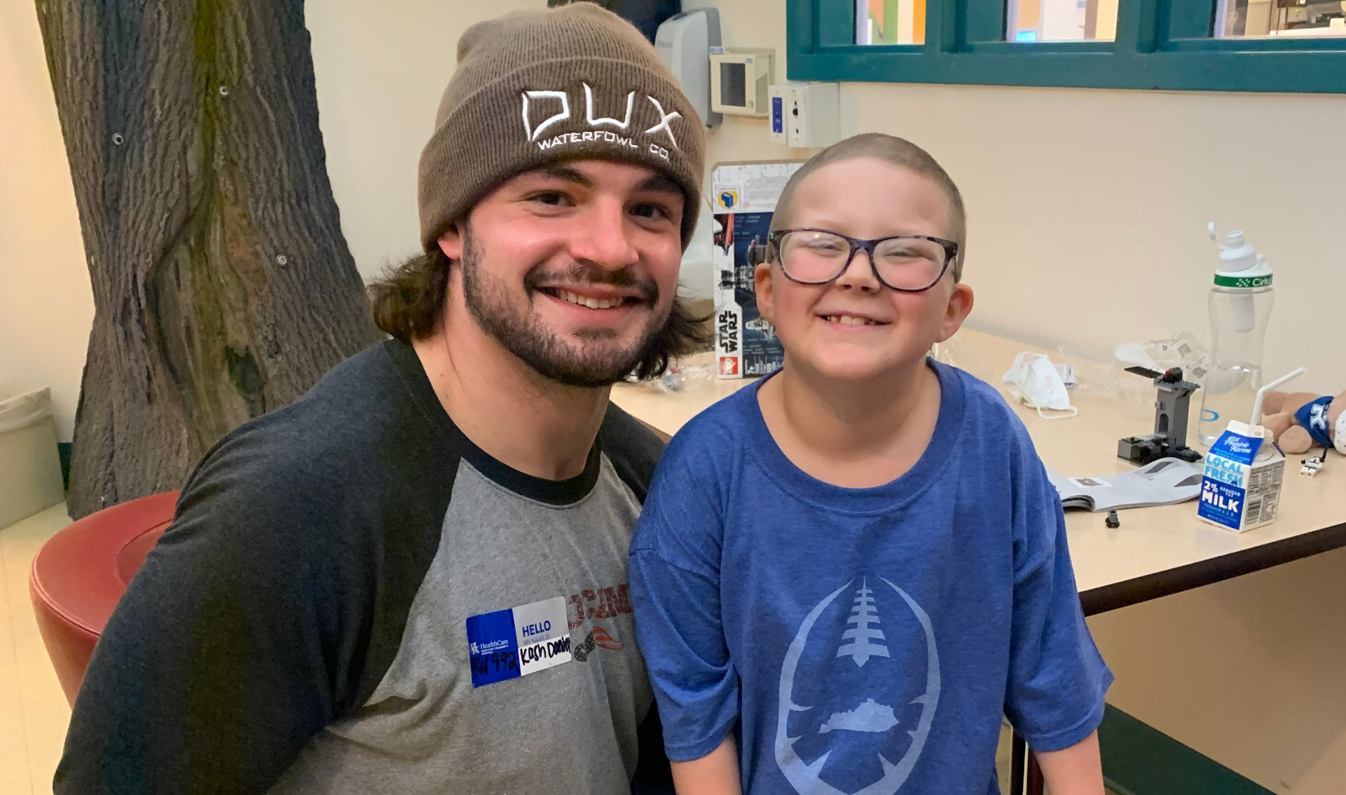 Ellie and Kash Daniel, a young man with an athletic build, brown hair, and a beard wearing a brown beanie and a gray and black t-shirt, sit together and smile for a picture.