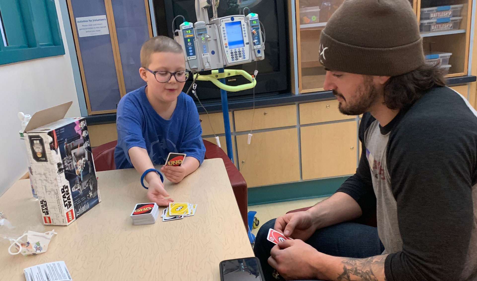 Ellie and Kash sit together at a table in the hospital and play Uno together.