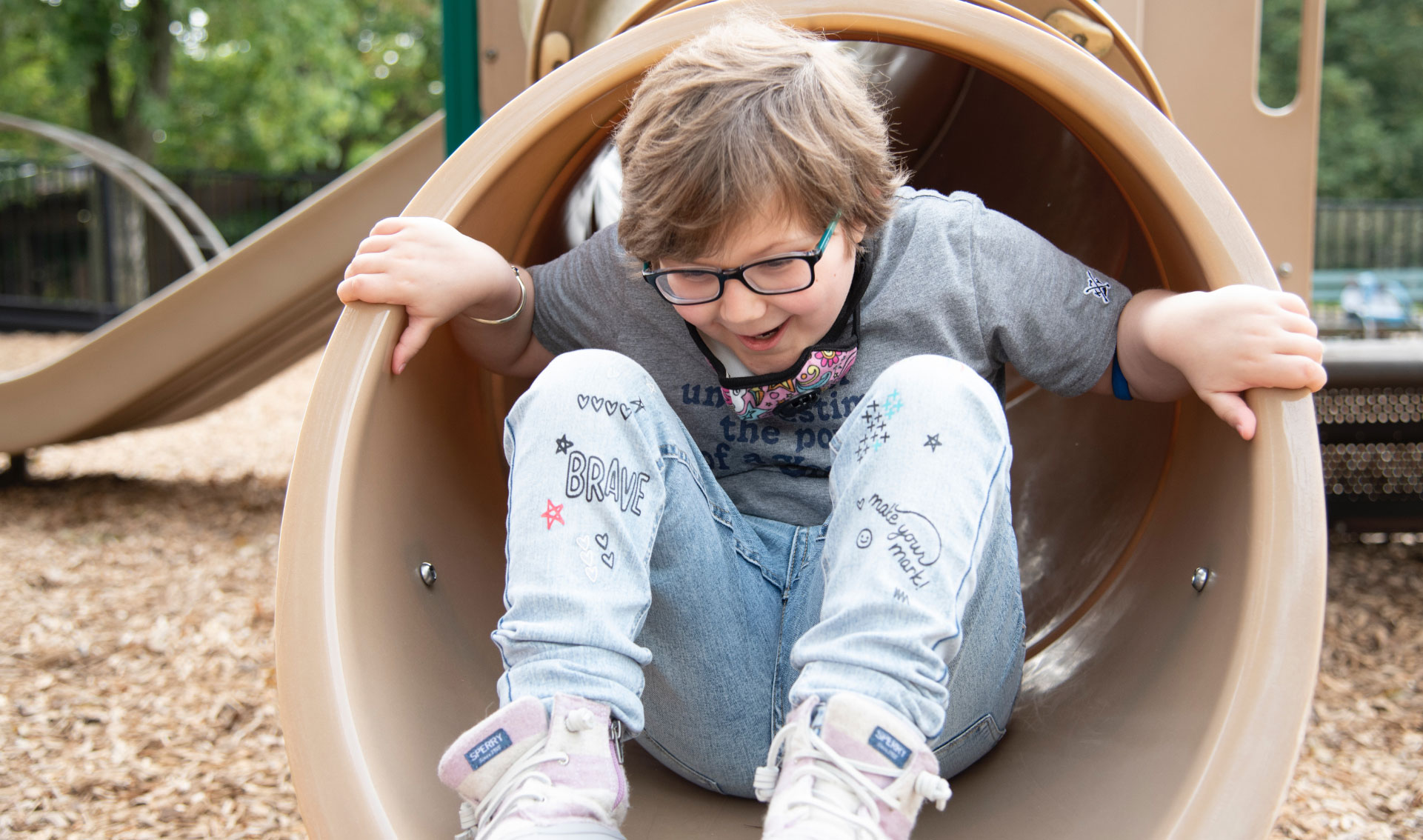 A photo of Ellie at the bottom of a tunnel slide with her hands grabbing the outside of the slide while she enthusiastically smiles. She is wearing a gray t-shirt, jeans, and light pink sneakers.