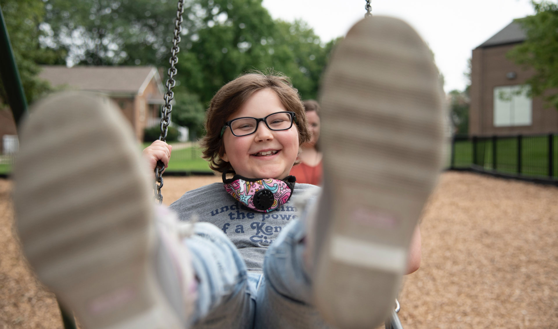 A close-up photo of Ellie swinging and smiling with her feet closest to the camera and blurred slightly. Her mother, Morgan, can be seen in the background.