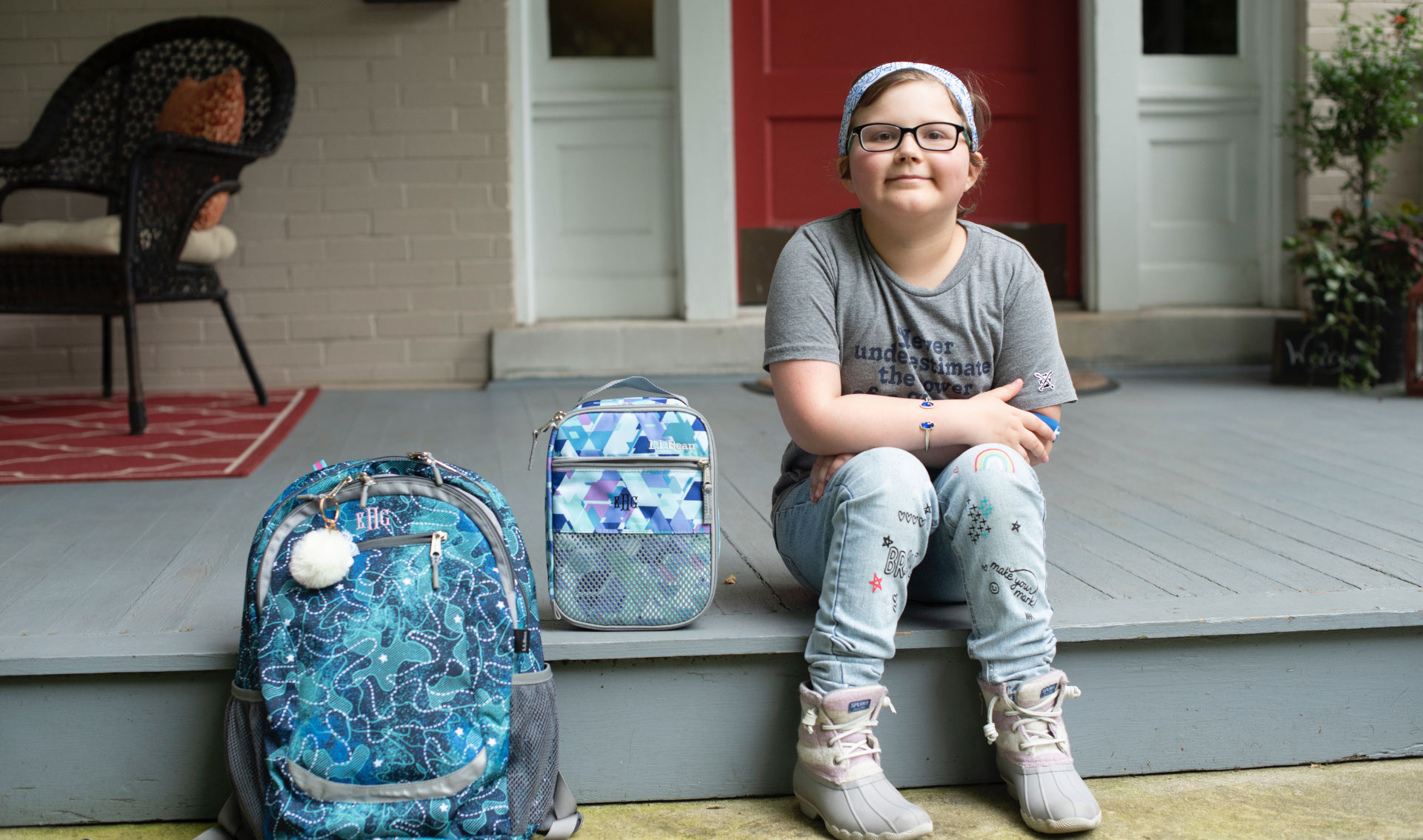 A photo of Ellie sitting on her front porch with her hands on her legs next to her school backpack and lunchbox.