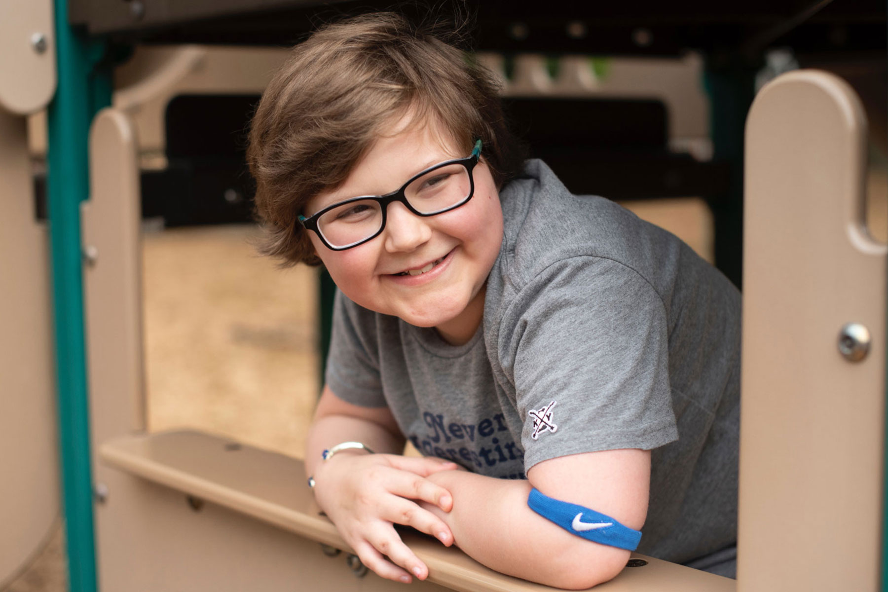 A portrait of Ellie Hurley, a young girl with short brown hair and glasses, wearing a gray t-shirt, posing on a playground. She is smiling while looking away from the camera.
