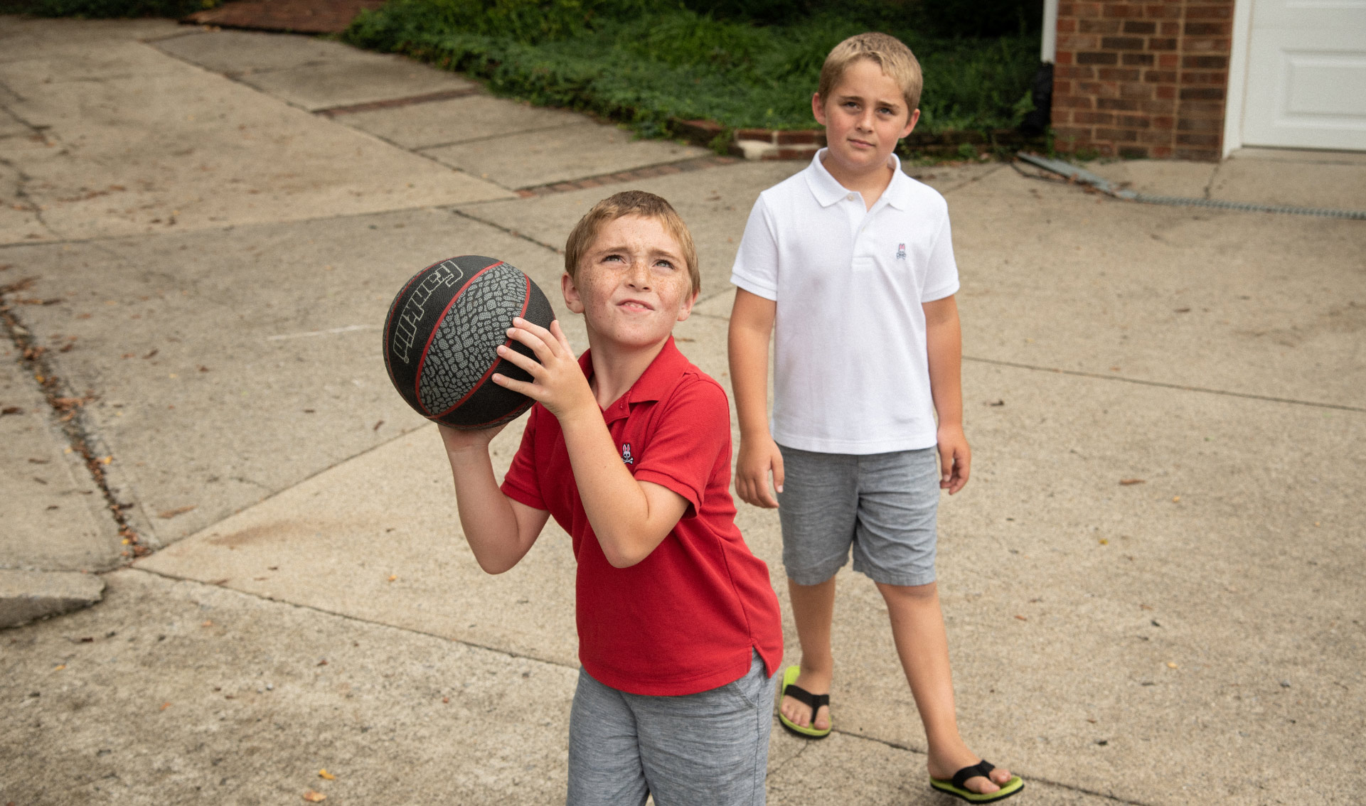 Max and his twin brother play basketball. Max is holding the ball and squinting up at the net, ready to shoot.