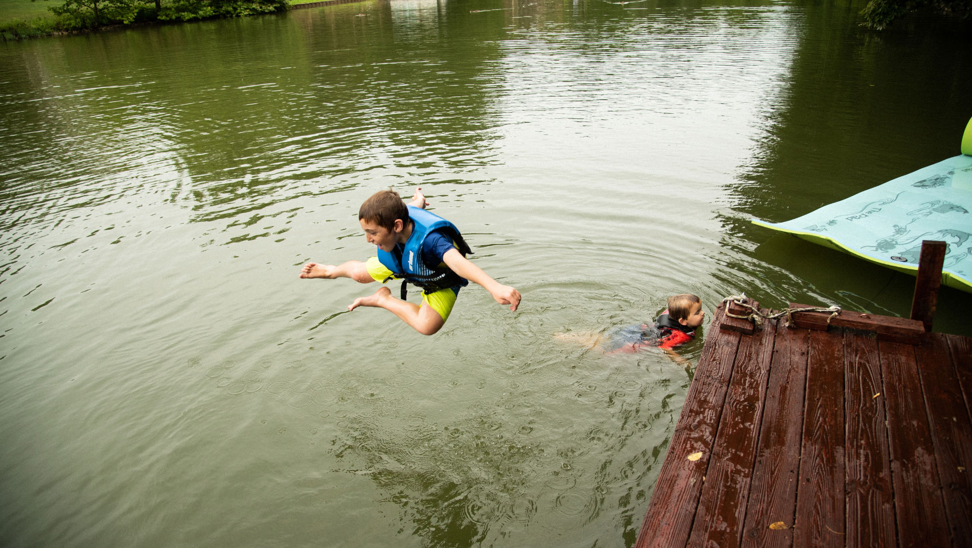 Max, wearing a life jacket, strikes a pose as he jumps off the dock into the lake. His younger brother, also wearing a life jacket, is visible in the lake at the end of the dock.