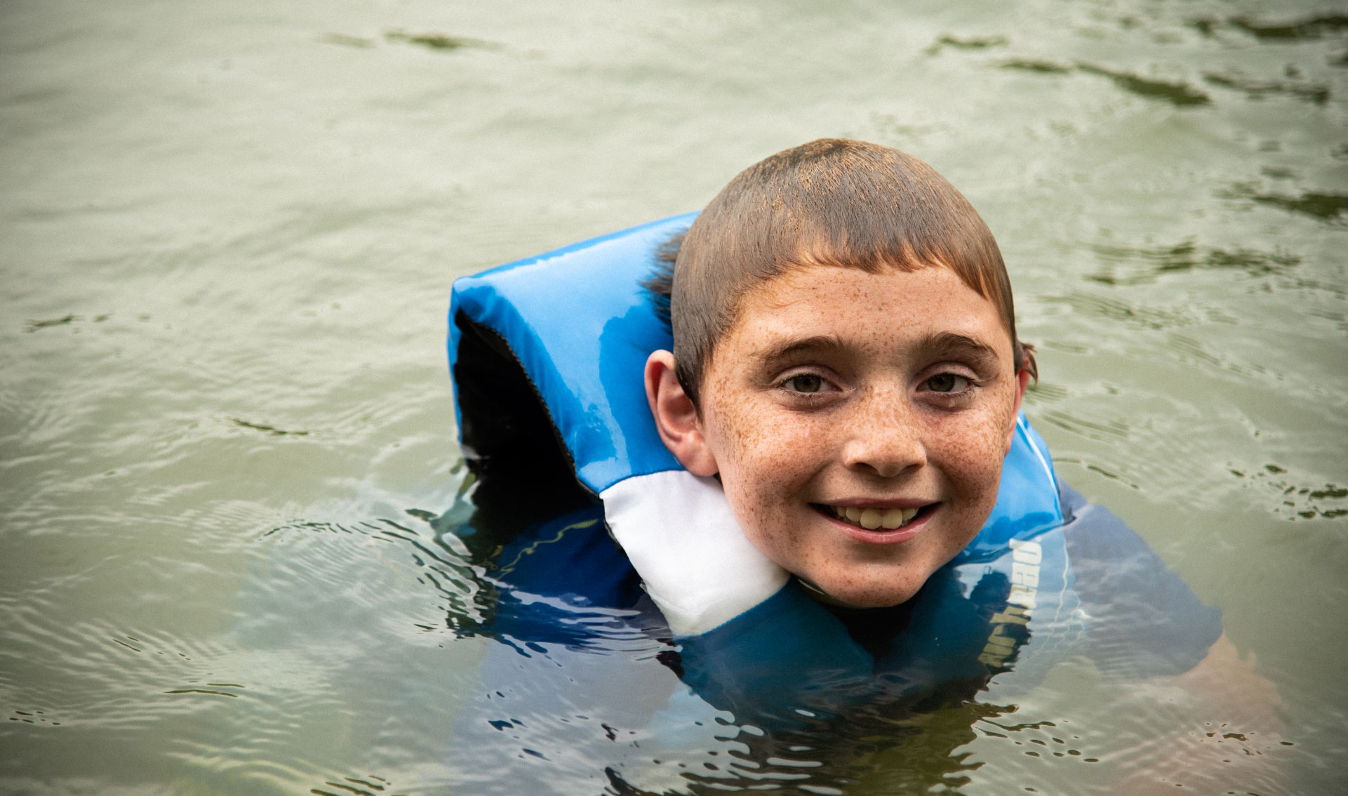 A portrait of Max, wearing a life jacket, floating in the lake. His hair is wet and he's smiling.
