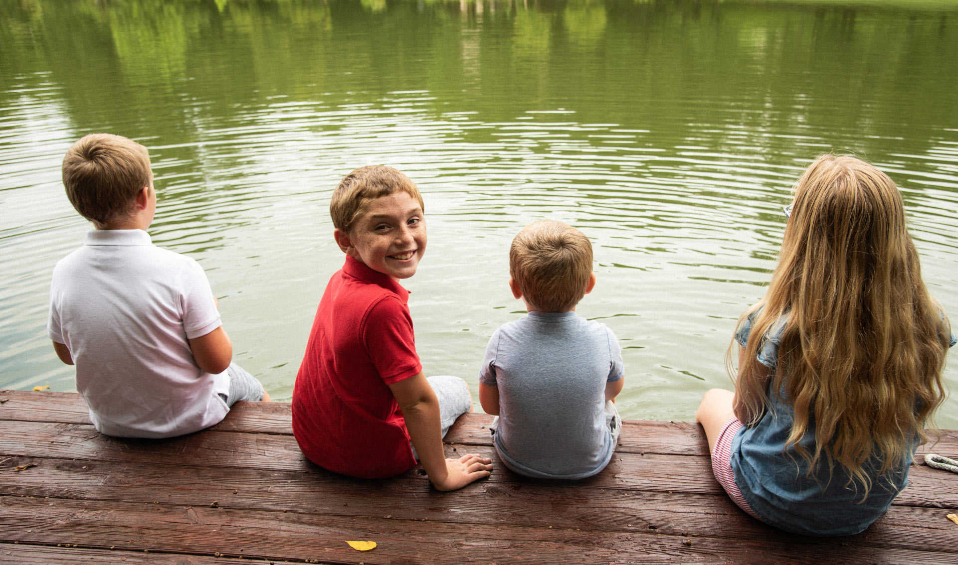 Max and his siblings sit on a dock. Max is turned to smile at the camera. His siblings are looking out at the lake.