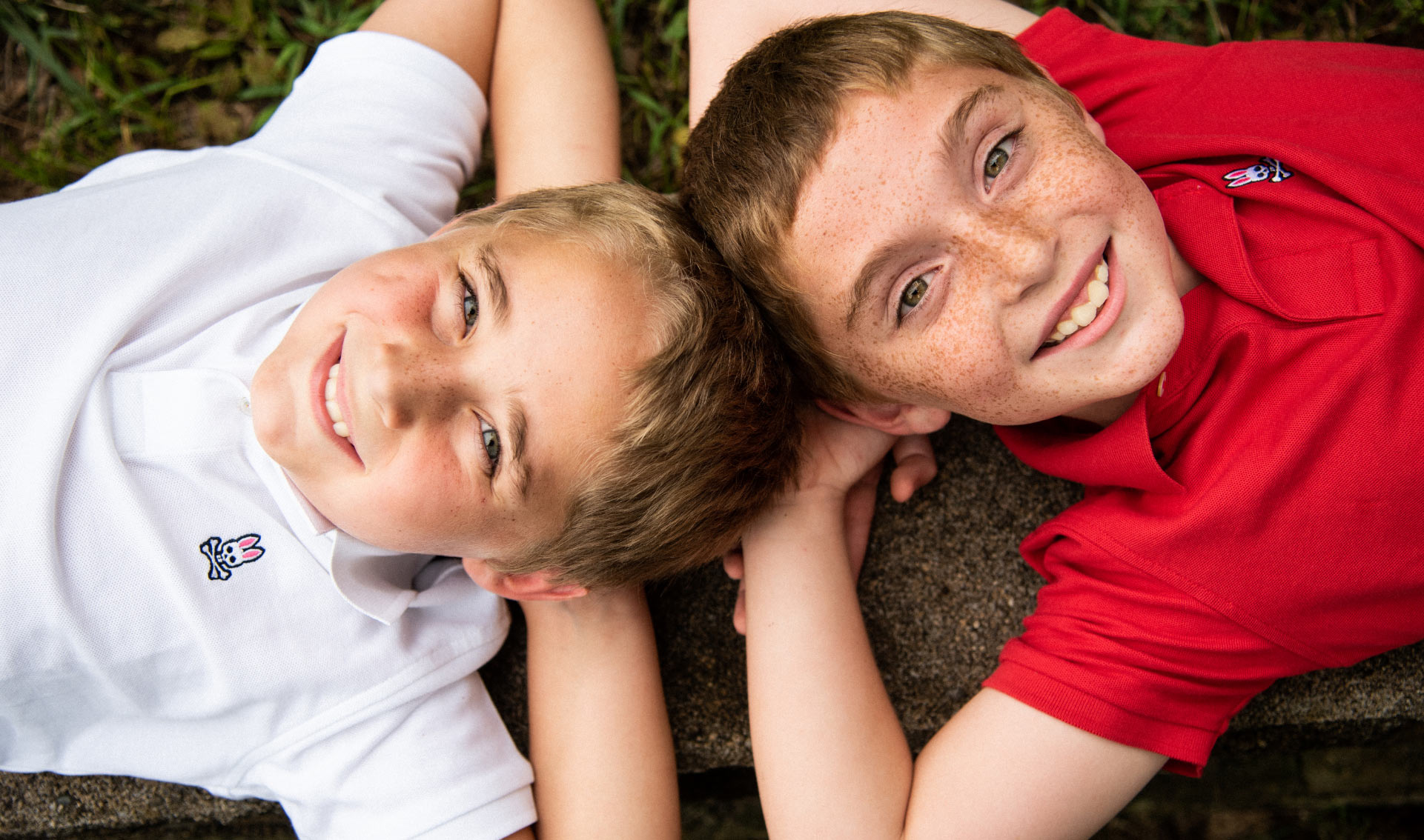 An overhead close-up shot of Max and his twin brother. Both are laying on the ground and have their hands behind their heads. Both are smiling.