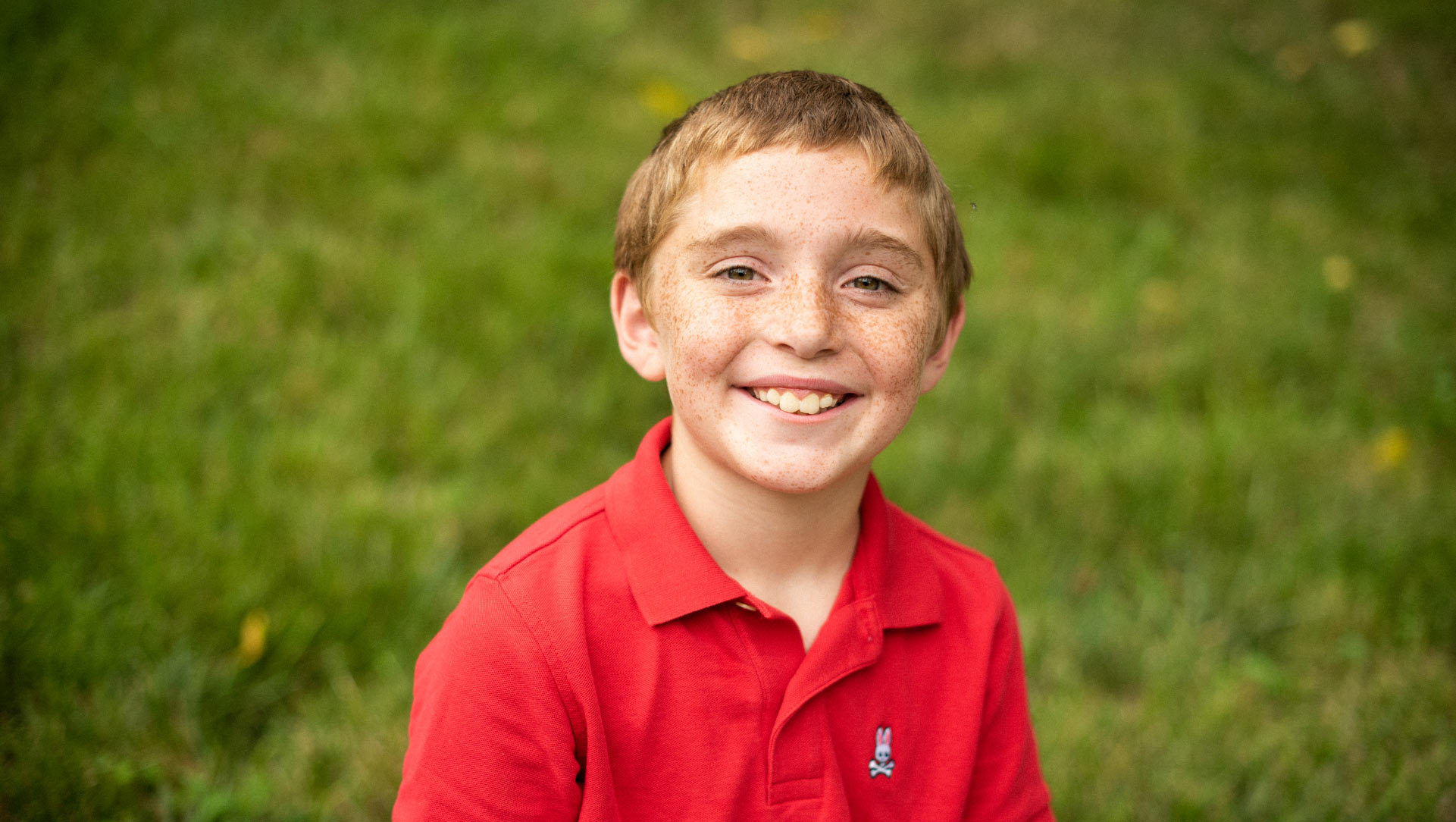 A portrait of Max, smiling broadly and wearing a red polo shirt.