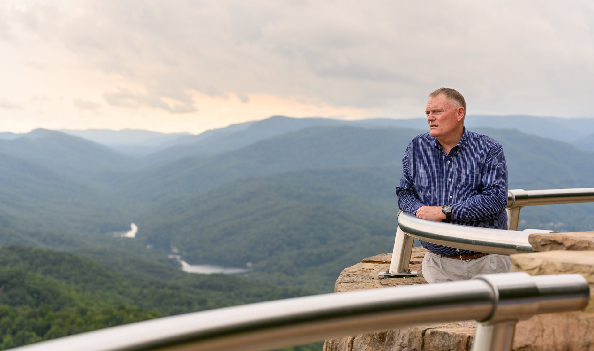 A landscape photo of Michael at an overlook, looking out across a view of the sky, mountains and trees.