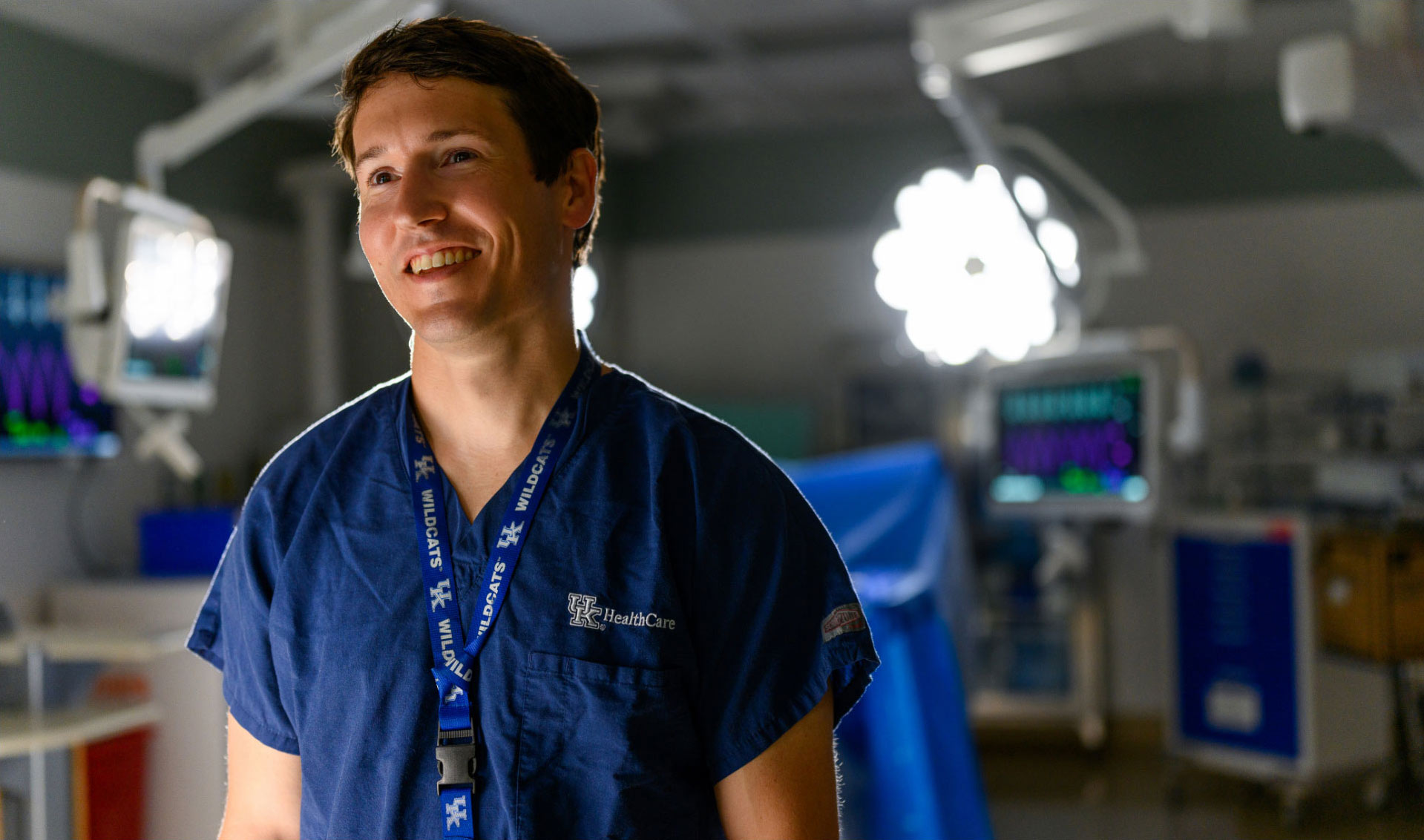 A portrait of Dr. James, a young-looking man with brown hair, dressed in blue scrubs, standing in a surgery room.