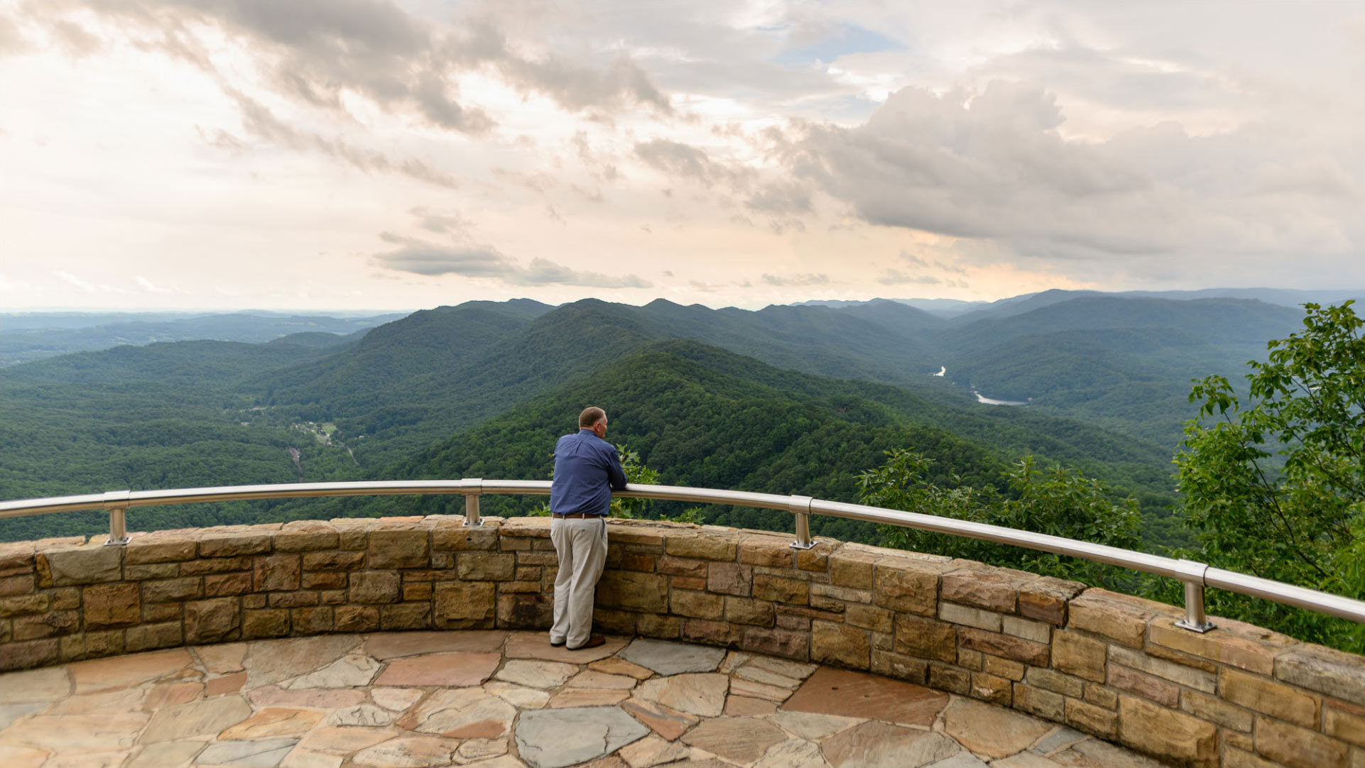 A landscape photo of Michael with his back facing the camera as he stands on a gated ledge that looks out over mountains and trees.