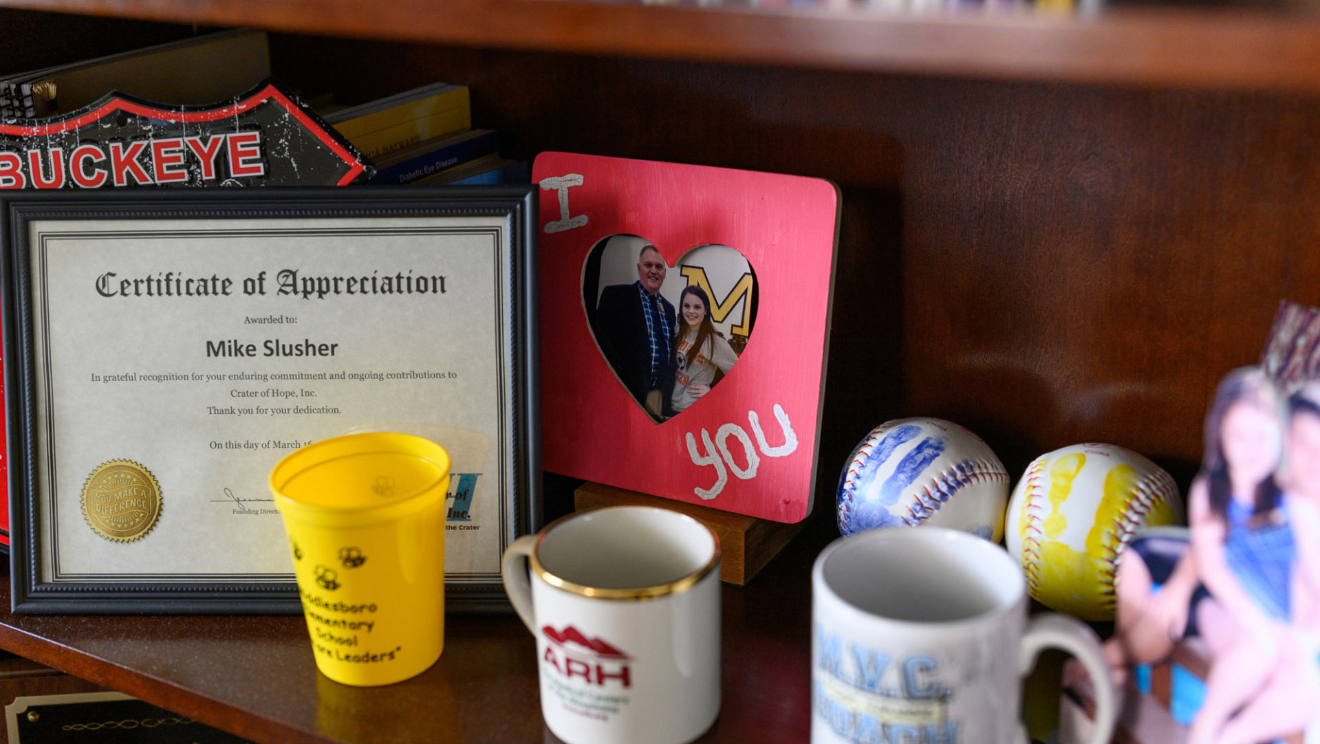 A close-up photo of a shelf featuring a framed picture of Michael and his daughter, mugs, baseballs and a certificate of appreciation.