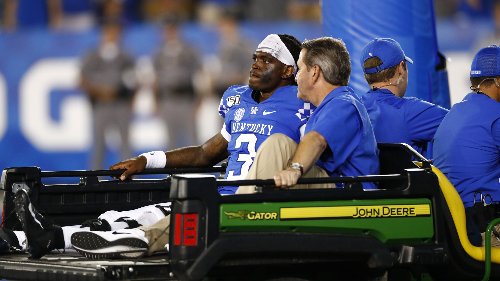Terry rides in the back of a golf cart off of the field after sustaining his injury. He is accompanied by a trainer, his facial expression is grim.