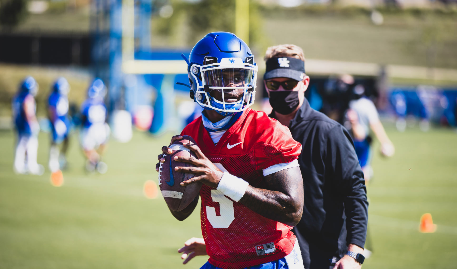 Terry, dressed in practice gear and in a red jersey to signify him as the quarterback, during a practice with a coach and fellow teammates in the background behind him.