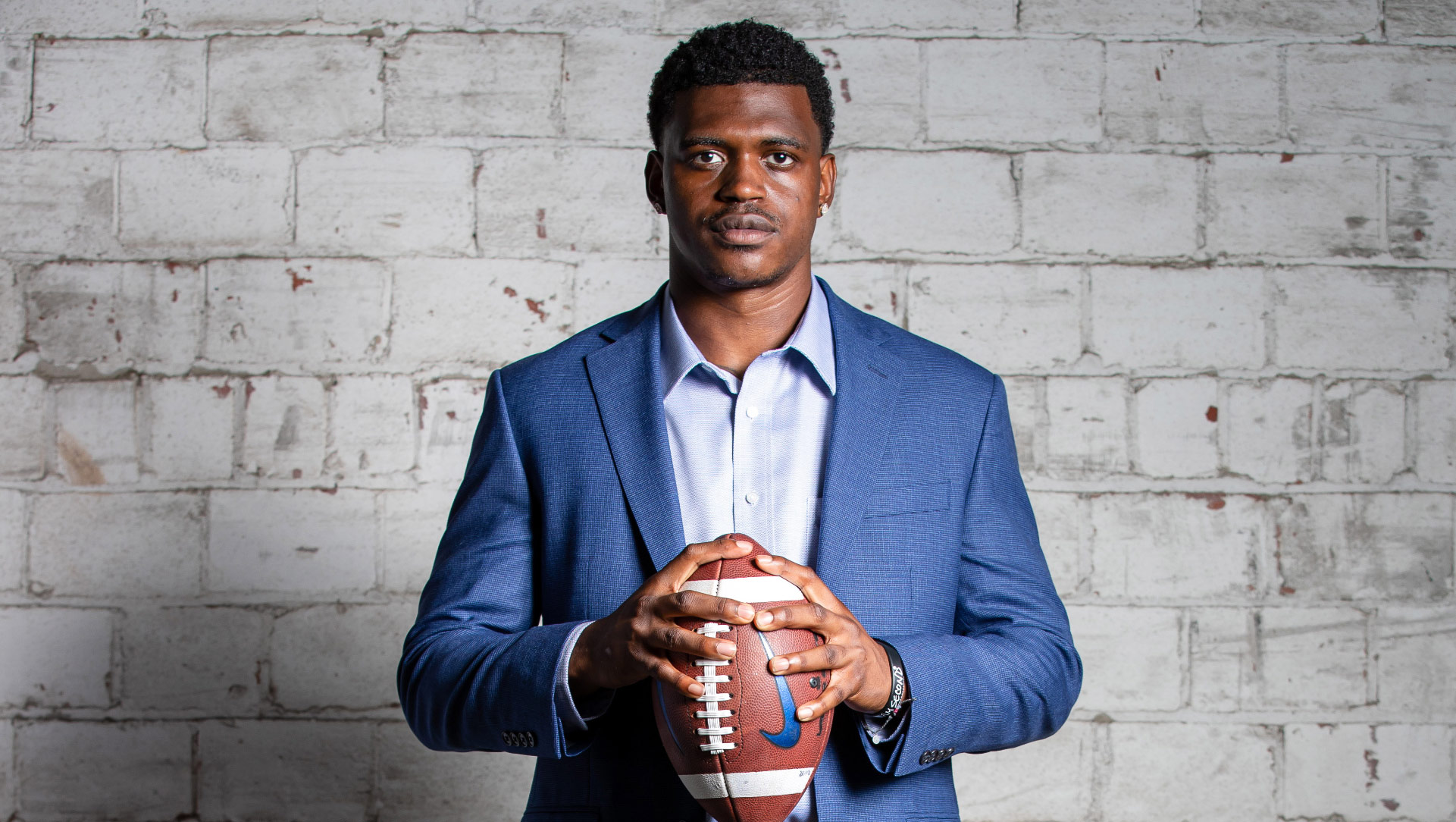 A portrait of Terry, dressed in a blue blazer and light blue button-up shirt, holding a football and looking directly at the camera.