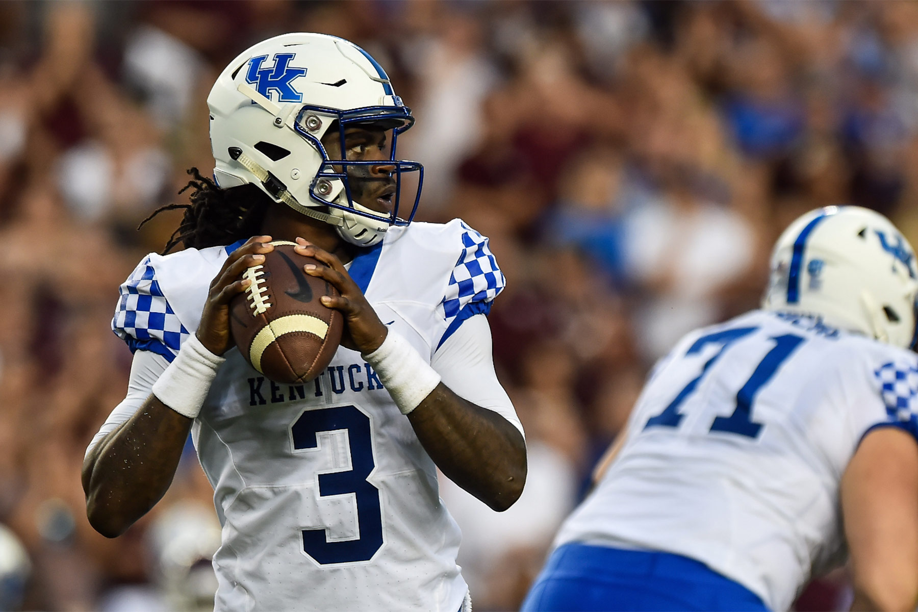 An action shot of Terry Wilson, a young, athletic Black man dressed in his football uniform and helmet, preparing to throw a football during a University of Kentucky game.