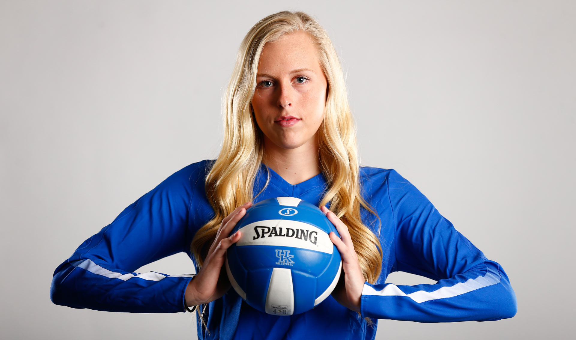 A portrait of Alli standing against a white backdrop, holding a volleyball between her palms. She looks determined and strong.