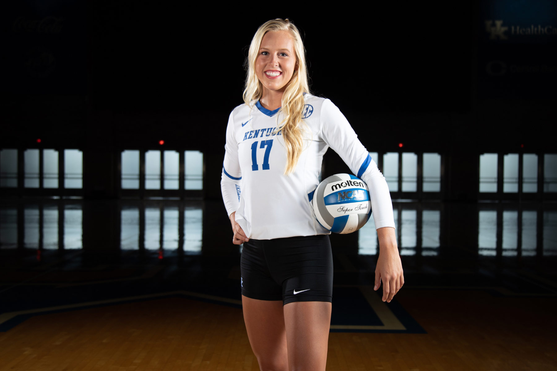 Alli Stumler, a tall white college-age girl with long blonde hair, poses in a gym. She is wearing a blue and white UK volleyball uniform and holding a volleyball under one arm. She is smiling.