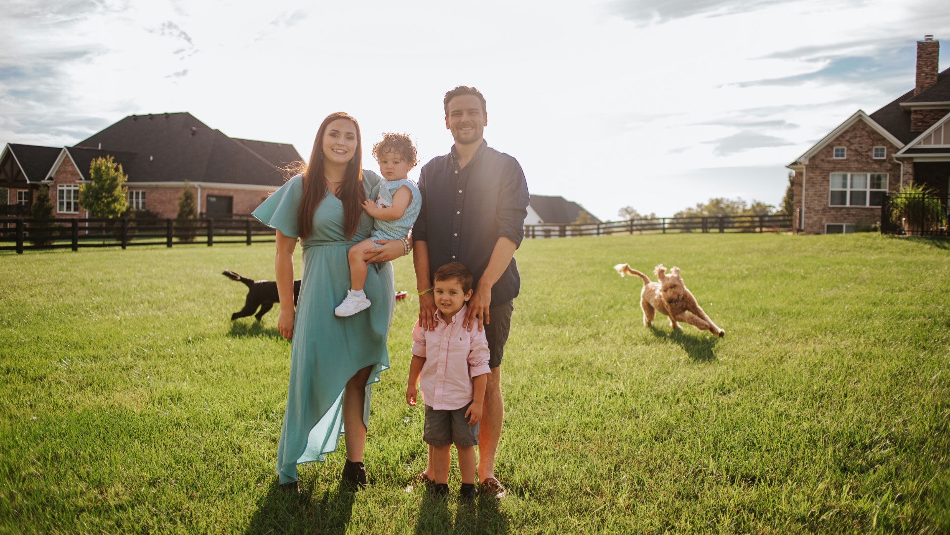 Charlie's family—including his mom, Cassidy, wearing a teal dress, his dad, Alex, wearing shorts and a navy button-down, and his brother, Baylor, wearing shorts and a pink button-down—poses for a family photo in front of their home as their two dogs run around them.