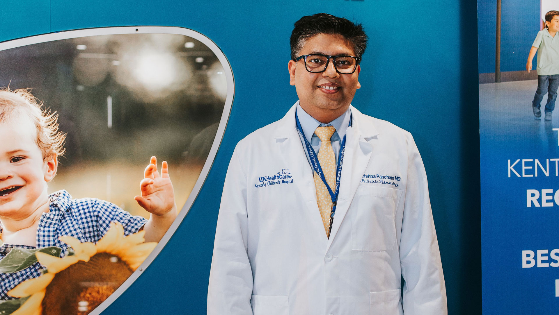 Dr. Krishna Pancham, a middle-aged south Asian man with black hair and black-rimmed glasses wearing a white doctor's coat, smiles at the camera.