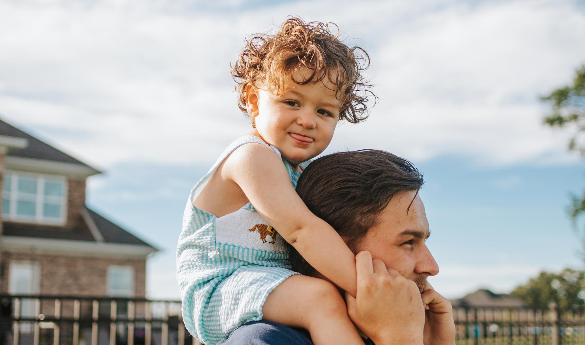 A close-up photo of Charlie sticking his tongue out while he sits on his dad's shoulders. His dad holds onto his hands.