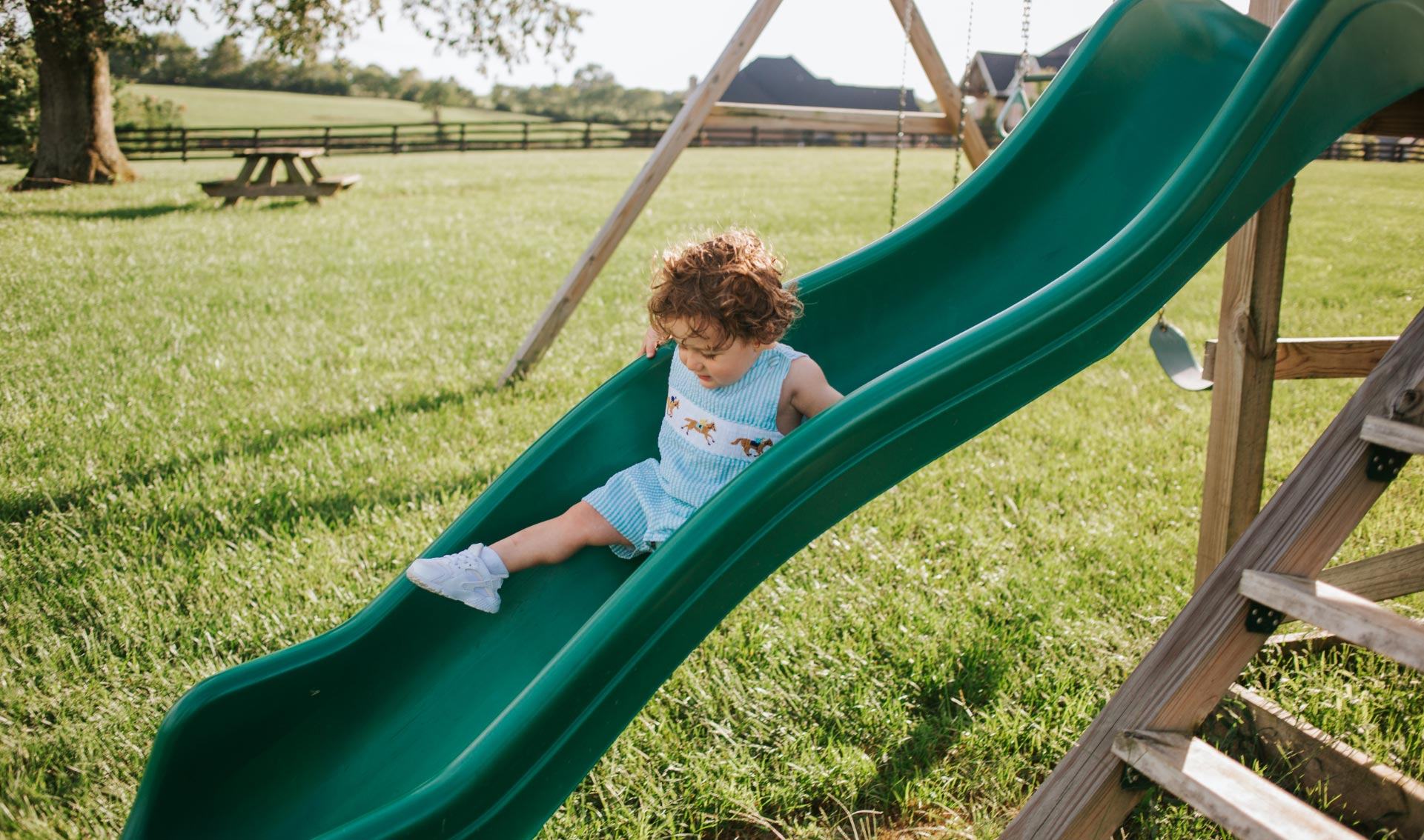 Charlie, dressed in a gingham overall set with horses on it, slides down a green slide attached to a wooden playground in the family's backyard.
