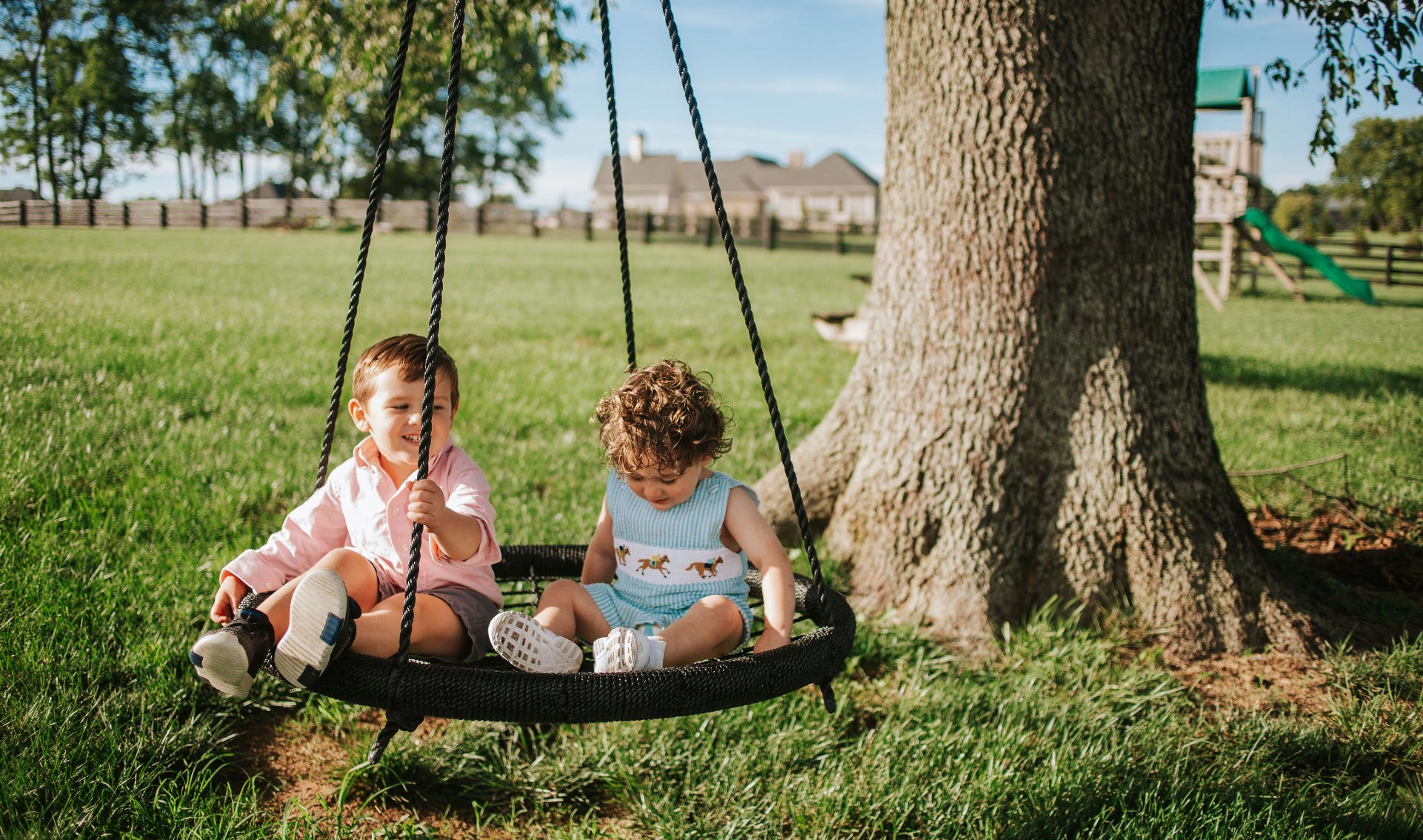 Charlie and his older brother, Baylor, sit on a netted swing in front of a tree. Both are smiling.