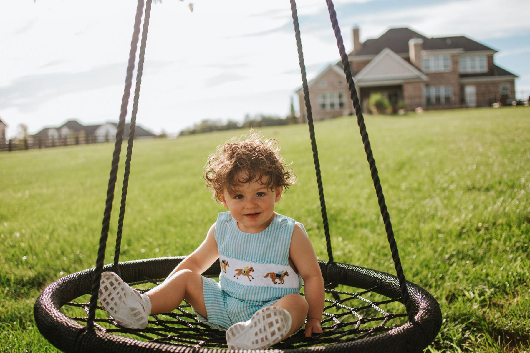 Charlie, a toddler-age boy with curly brown hair dressed in a green striped onesie, sits on a netted swing with a large home and yard in the background.
