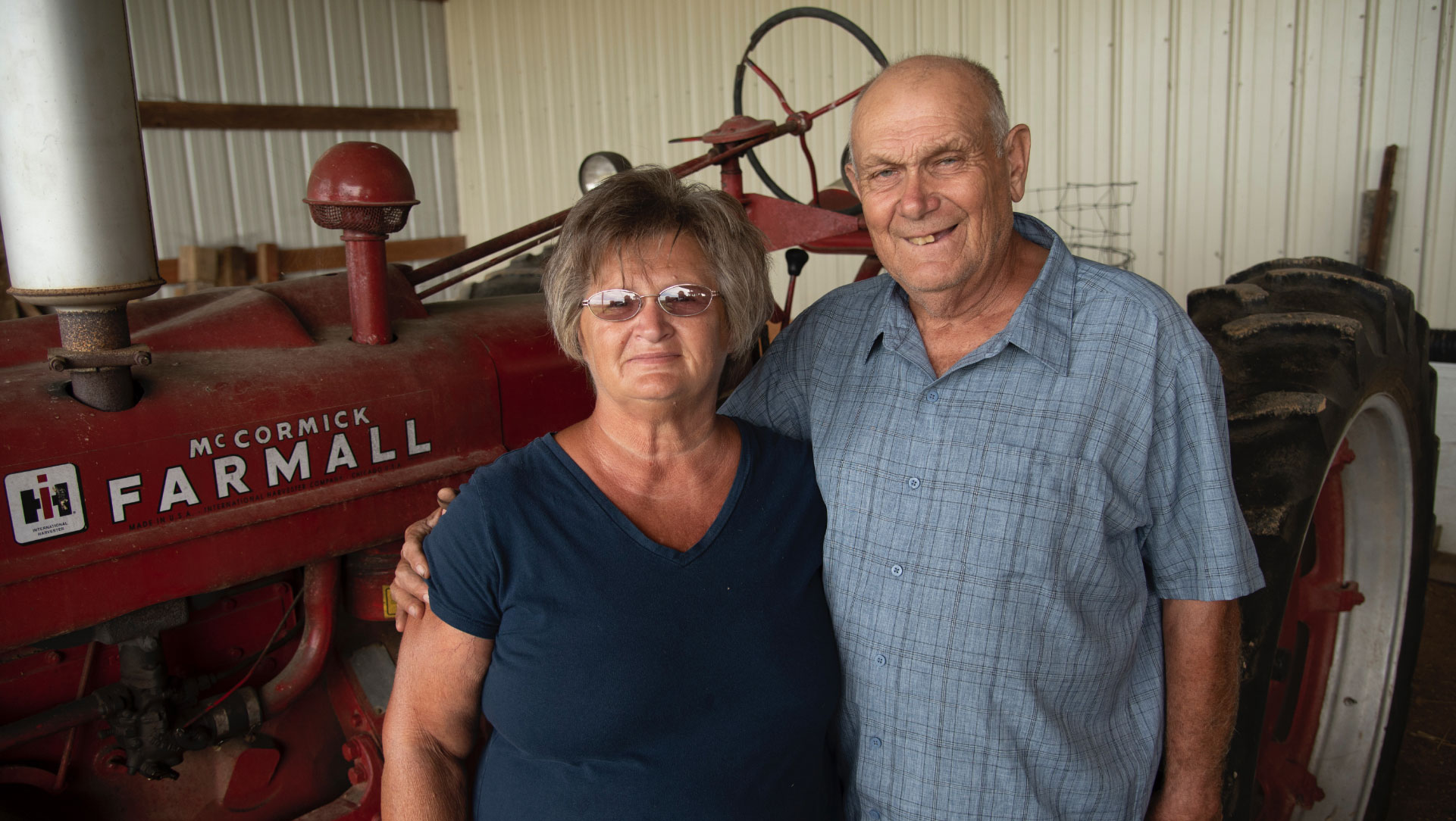 Charlotte and her husband, an older man in a blue button-up shirt, posing for a photo in front of an older red tractor.