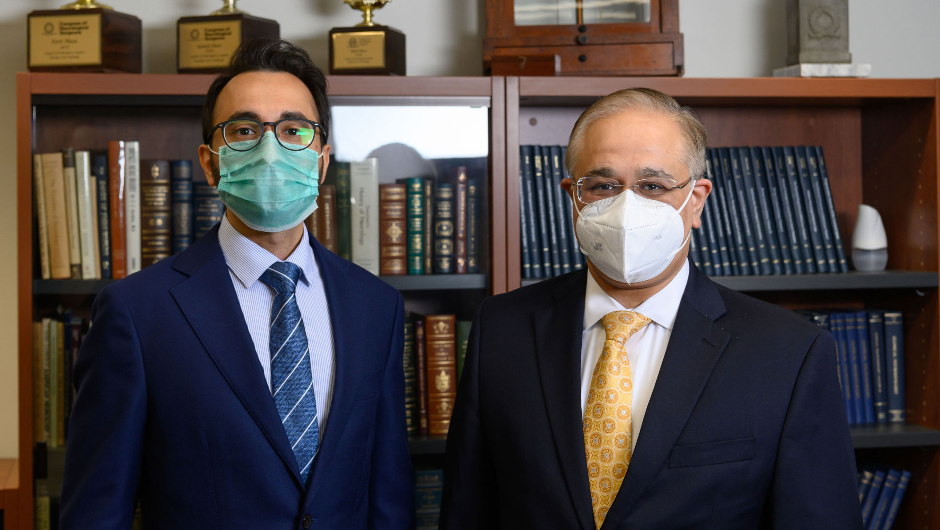 Dr. Farhan Mirza (left), a younger man with dark hair and a beard with glasses, and Dr. Siddharth Kapoor (right), a middle aged man with glasses, both dressed in suit jackets and ties with face masks on standing side by side in front of a bookshelf.