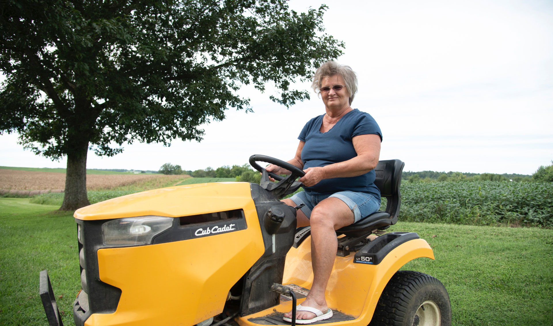 A photo of Charlotte smiling at the camera as she drives a yellow riding lawn mower.