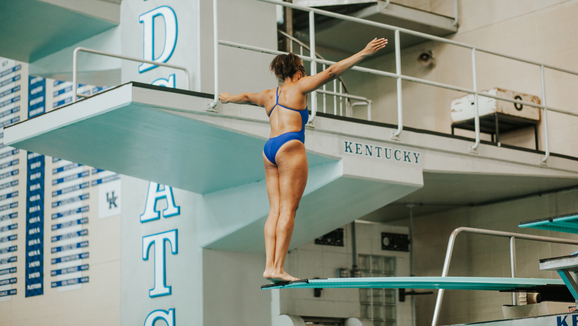 An action shot of Jaida as she stands on the very edge of a high dive, her legs straight and her arms extended fully, preparing to dive into the pool below her.