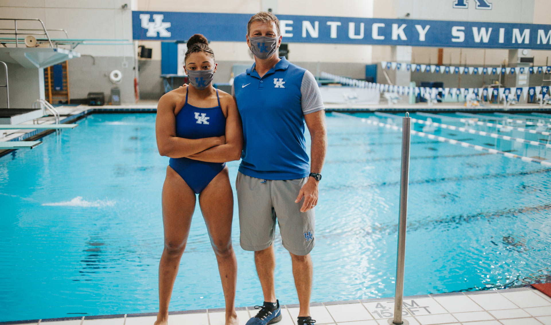 Jaida poses for a photo on the side of the pool with her coach, Ted Hautau, a middle aged man with blonde hair wearing a blue University of Kentucky polo and khaki shorts. Both are wearing masks.