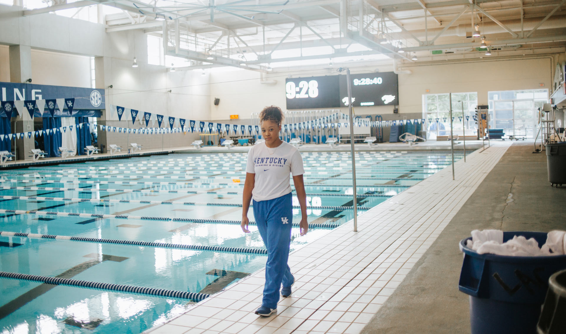 A photo of Jaida, dressed in a white t-shirt and blue track pants, walking alongside the pool.