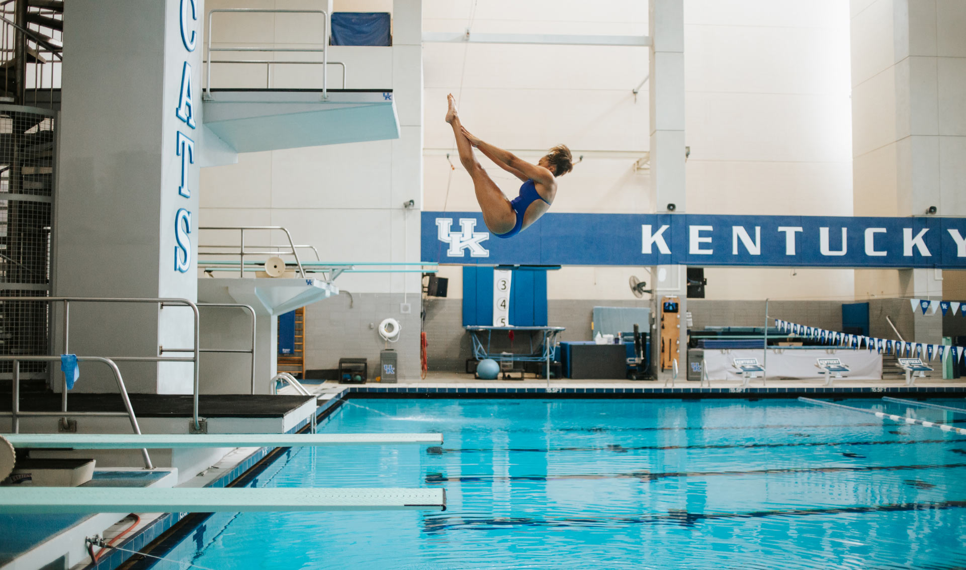 A photo of Jaida mid-dive, her body in the shape of a 'V' as she flips backwards into the pool.