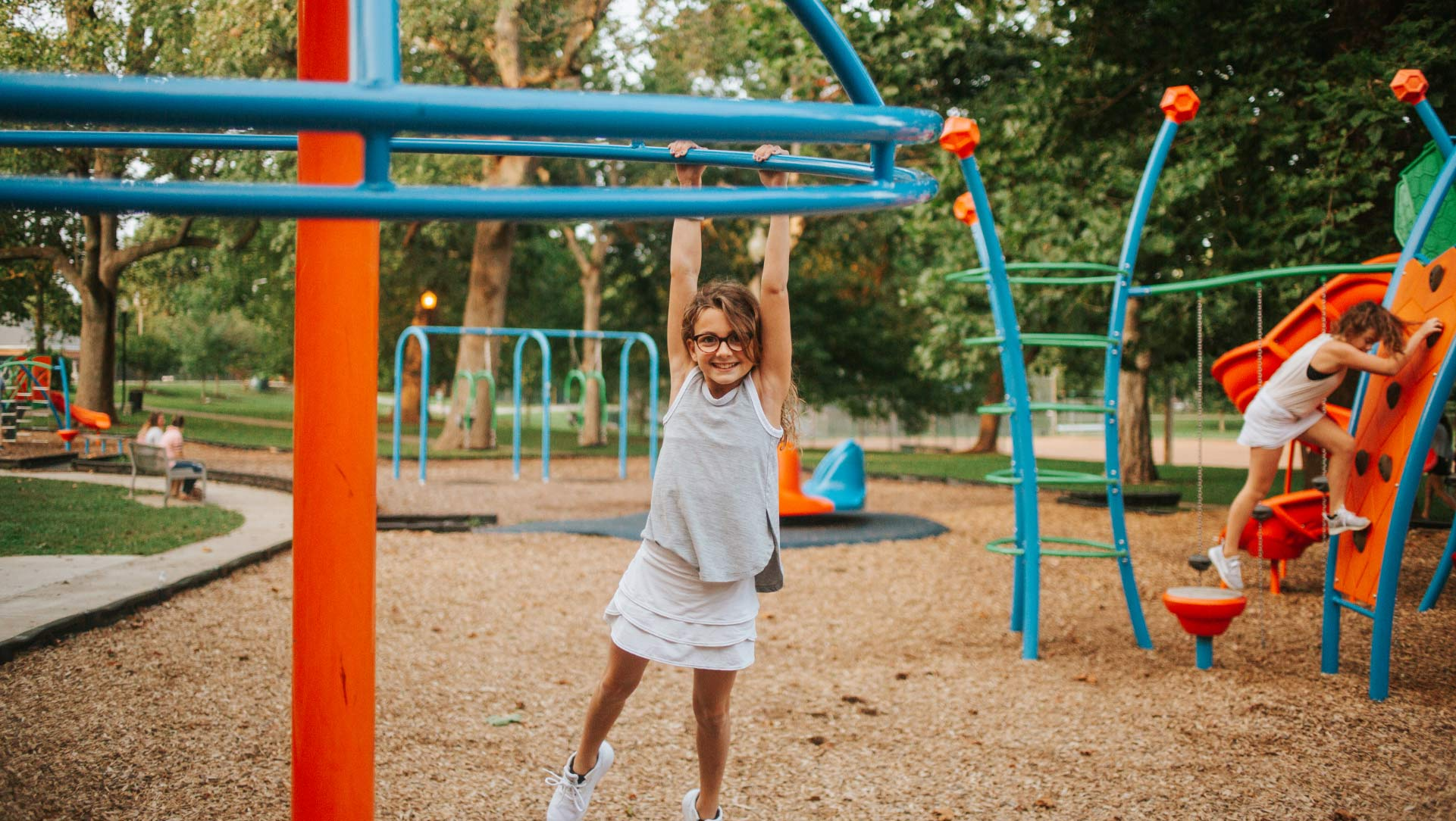 Gabriella Buffano, approximately 10 years old, holds onto a piece of playground equipment, swinging by her arms and grinning. She is wearing a white skirt, a gray tank top, and glasses.